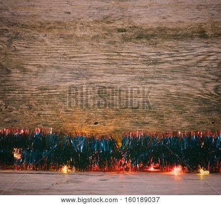 Festive Christmas background. blue tinsel and lights garland on a old barn boards. Tinted photo