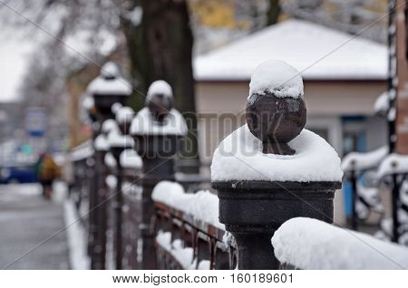 Vintage Black metal fence with round decorative elements covered with snow in perspective.