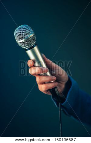 Elegant female journalist conducting business interview or press conference hand with microphone
