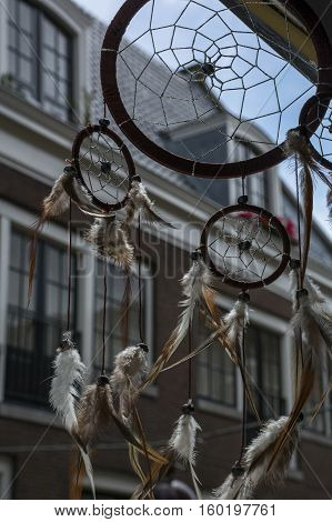 Dream catcher on the window with brown house as background