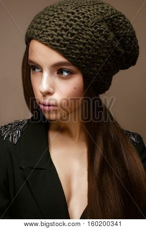 Beautiful girl in winter knit hat and khaki jacket. Young model with gentle makeup and colored arrows. Warm winter picture. Beauty face.