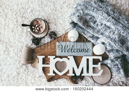 Winter homely scene, scandinavian style. Warm knit sweater, candles, cup of sweet cocoa with marshmallows and other decor on tray in bed. Wooden craft letters Welcome Home. Lazy cold weekend.