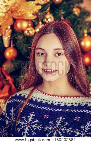 Beautiful smiling  girl sitting near Christmas tree.