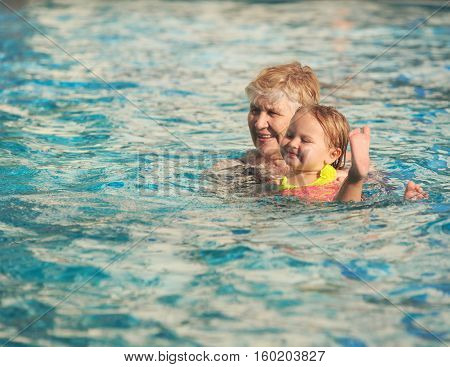 Grandmother and granddaughter swimming at pool, active retirement