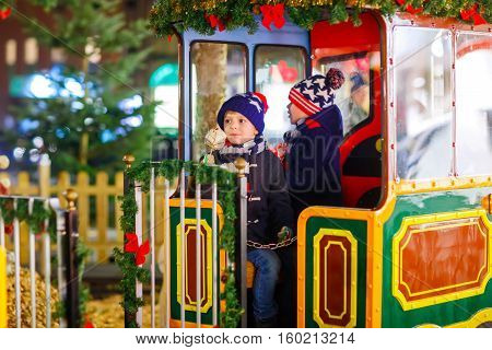 Two little kids boys on a carousel at Christmas funfair or market, outdoors. Happy children having fun and eating sweets. Traditional xmas market in Germany, Europe. Holiday, lifestyle concept.