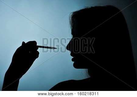 Syringe And Girl Silhouette On A Blue Background