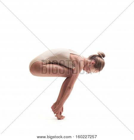 young beautiful dancer in beige swimsuit posing on isolated white studio background