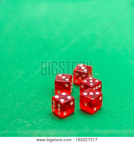 playing five red dice on a green background