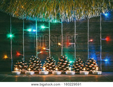 Festive Christmas new year concept. Colorful lights of garlands fir cones and candles on the background of old barn boards. Tinted photo