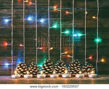 Festive new year and Christmas concept. Multicolored lights garland fir cones and candles on the background of old barn boards. Toning photo