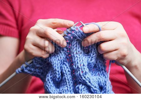 Knitting. female hands with needle and thread