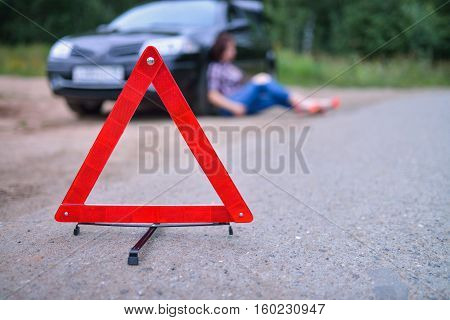 Warning sign triangle and woman with her broken car at background.