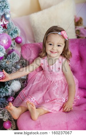 Very nice charming little girl blonde in pink dress sitting on a child's armchair and laughs loudly the background of Christmas trees in bright interior the house.
