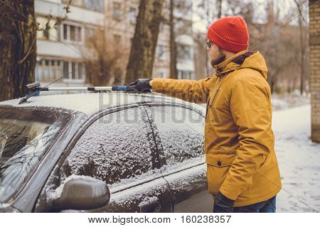 Man cleaning snow from car windshield with brush. Removing snow from car