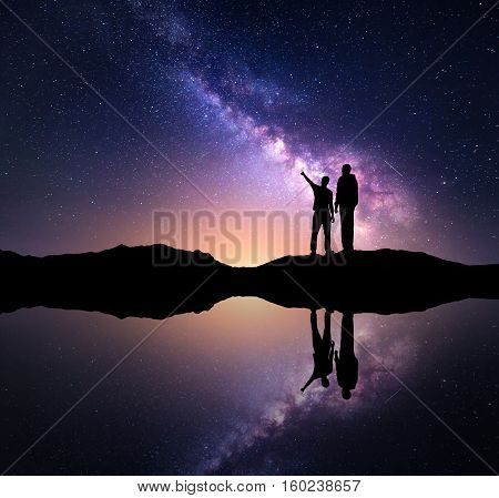 Milky Way with silhouette of a family. Father and a son who pointing finger in night starry sky on the mountain near the lake with sky reflection in water. Night landscape. Space. Milky way with men