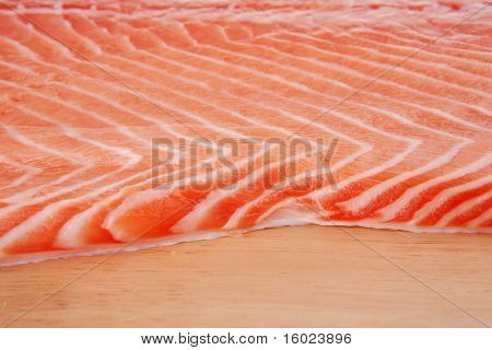 fresh raw salmon fillet on wood over white