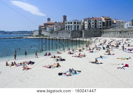 Antibes France - June 2 2007: city beach of Antibes with unidentified people sunbathing. Antibes is a Mediterranean resort in the Alpes-Maritimes department of southeastern France on the Cote d Azur