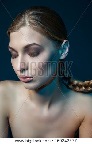 Studio shot of young model keeping eyes closed with cheek and ear painted in blue color.