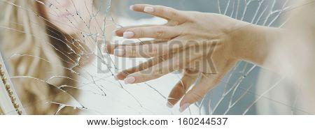 Hand of depressed woman on elegant broken mirror