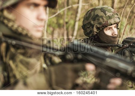 Masked soldiers with weapons learning about military strategy and tactics outdoor