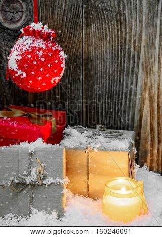 Christmas Vintage Background with gift boxes wrapped in kraft paper, candle and snow
