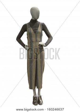 Full-length female mannequin dressed in brown overalls and pullover isolated on white background. No brand names or copyright objects.