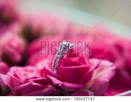 Sparkling diamond engagement ring in one of small pink roses great for valentines.
