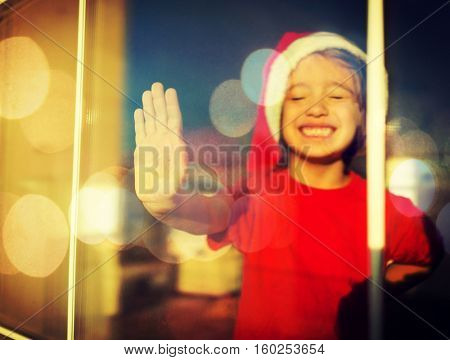 Little boy on winter window looking outside and waiting for winter holidays happy moments and fun (noise added for the effect)