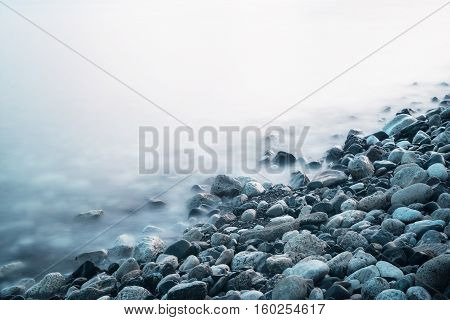 Dreamy natural background with sea shore, rocks and waves. Long exposure. Black and white