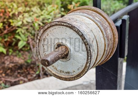 Close up of old dumbbell. Outdoor view in the park (healthcare, sport, fitness)