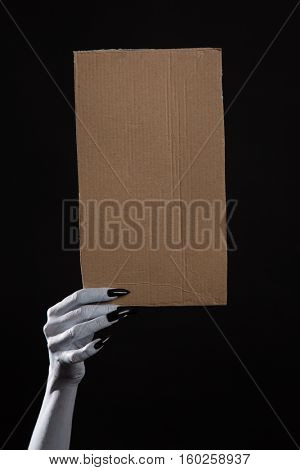 White ghost hand with black nails holding blank cardboard, Halloween theme