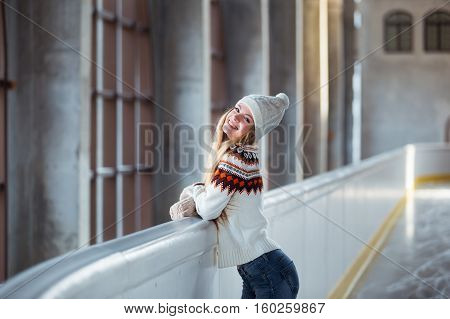 Autumn Winter portrait: Young woman dressed in a warm woolen cardigan, gloves and hat posing outside in a skating park