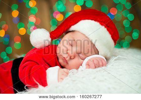 Portrait of newborn baby boy in Santa clothes lying under Christmas tree