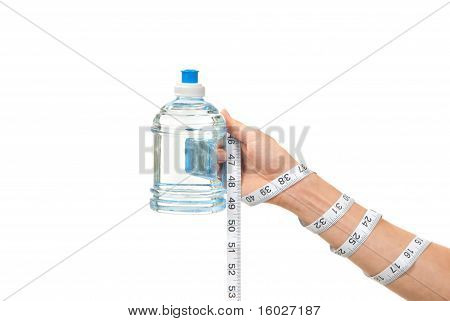 Tape Measure Is Twisted Around Hand With Bottle Of Water