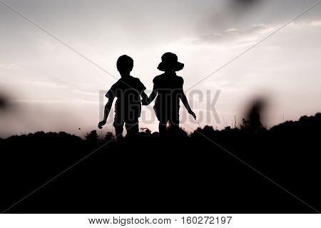 Silhouettes of kids jumping off a cliff at sunset. Little boy and girl jump high holding hands. Brother and sister having fun in summer. Friendship freedom concept. Fraternal twins on vacation in mountains.