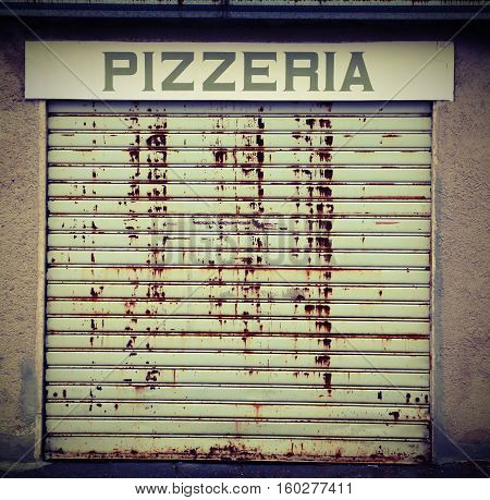 Italian Pizzeria with the huge sign and the gate closed