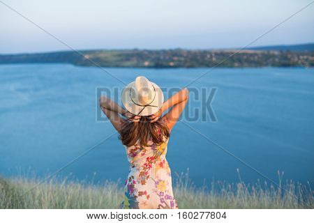 Outdoor summer hipster back view portrait of young woman wearing a hat enjoying the view on lake