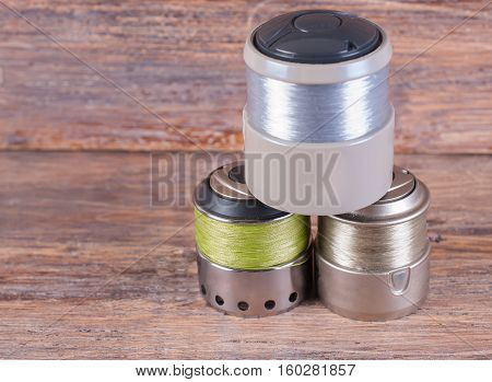 Spool wound with a fishing line for spinning reel . Wooden background