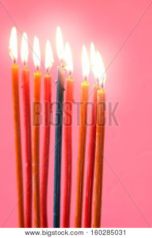 Hanukkah burning candles on the pink background vertical