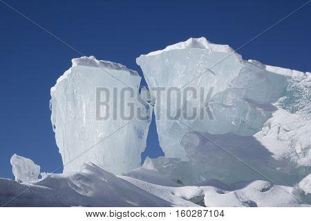 Huge blocks of aqua ice on blue sky background. Winter backdrop.