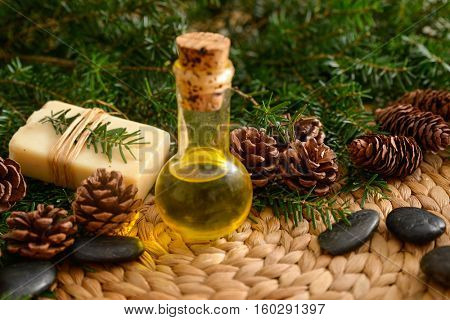 Christmas fir tree with oil ,soap and stones on wicker woven mat on mat