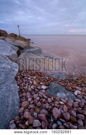 A pile of stones. Breakwater with a beacon. The coast of the English Channel. Sidmouth. Devon. England