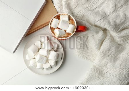 Cup of fresh coffee with marshmallow  and knitted plaid, top view