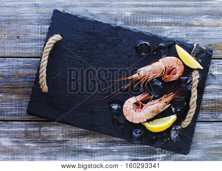 raw prawns with lemon and ice on a black coal board on a wooden table, selective focus