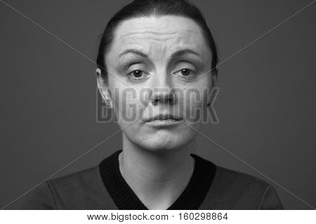 Young woman looking pained and disappointed close up black and white
