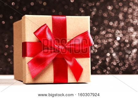 Present box with red bow on black sparkling background. Festive concept for Christmas