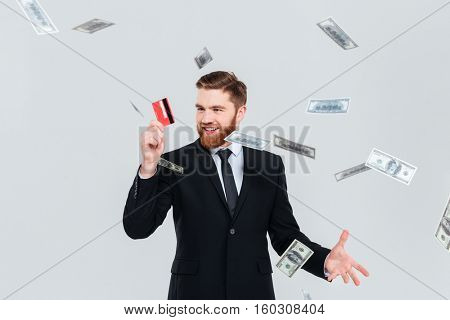 Happy bearded business man in black suit with credit card and falling money. Isolated gray background