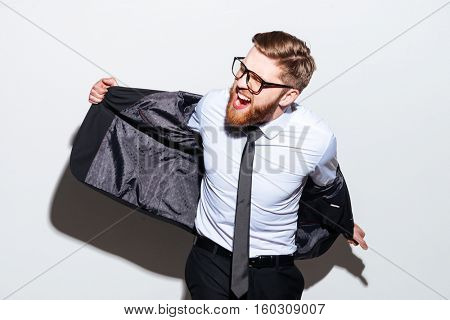Bearded Business man in glasses taking off his jacket and looking aside. Isolated gray background