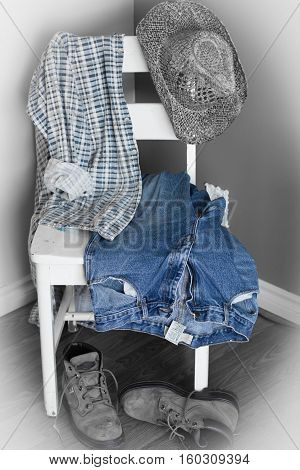 vertical image of a cowboys denim jeans and checkered shirt and cowboy hat and boots all hanging over a white chair.