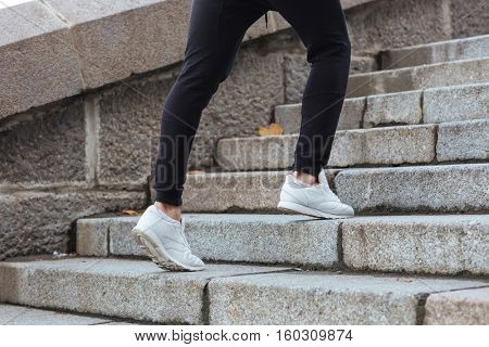Closeup of man legs running on stairs outdoors